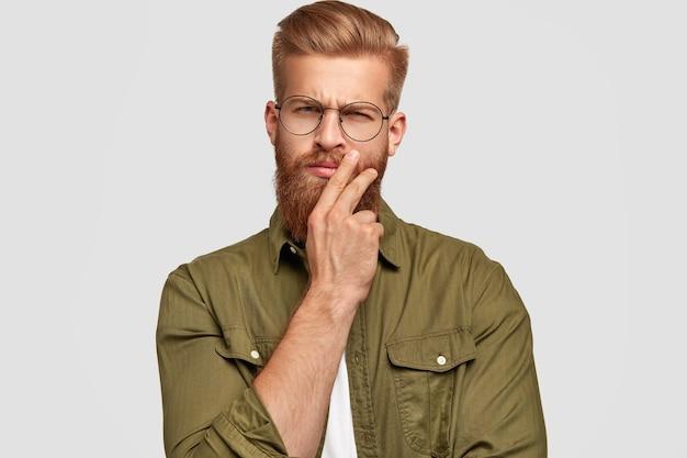 Nadenkend gember mannetje houdt kin, kijkt met serieuze uitdrukking, trendy kapsel heeft, besluit, gekleed in modieus shirt, geïsoleerd over witte muur. mensen en gezichtsuitdrukkingen