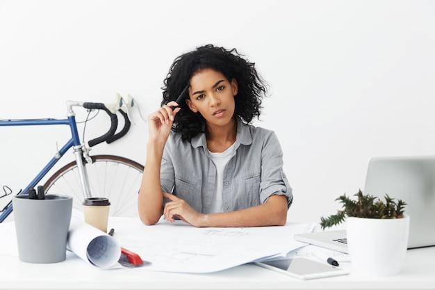 Nadenkend gemengd ras vrouwelijke student architect met zwart krullend haar hoofd krabben met potlood