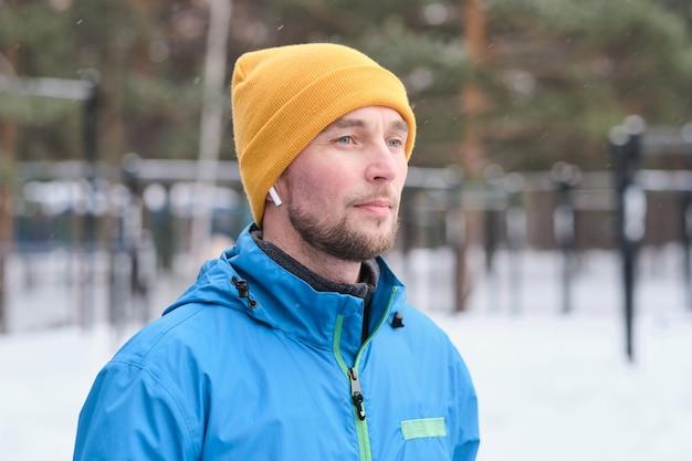 Nadenkend gemotiveerde jonge sportman met stoppels luisteren naar muziek in de oordopjes terwijl hij buiten in de winter staat