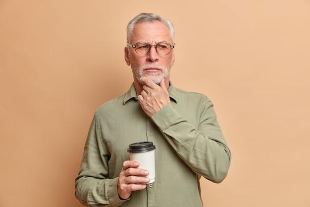 Nadenkend gerimpelde man staat in bedachtzame houding wrijft over de kin en probeert zijn geest ergens over na te denken terwijl hij een koffiepauze heeft, draagt een optische bril en een formeel overhemd