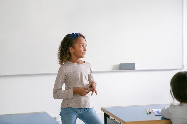 Nadenkend glimlachend afrikaans amerikaans schoolmeisje dat zich bij whiteboard voor klasse bevindt