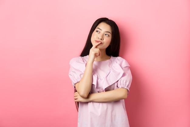 Nadenkend glimlachend aziatisch meisje dat een keuze maakt, het logo in de linkerbovenhoek bekijkt en denkt, een idee heeft, sluw op roze achtergrond staat.