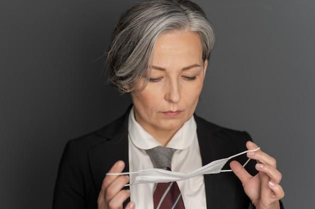 Nadenkend grijs-haired zakenvrouw zetten een beschermend masker op haar gezicht naar beneden te kijken. portret close-up. pandemisch concept. bescherming concept