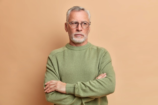 Nadenkend grijs harige bebaarde oude man staat met gekruiste armen en kijkt bedachtzaam weg, draagt een casual trui, overdenkt plannen voor weekend gaan kinderen bezoeken geïsoleerd over bruine studiomuur