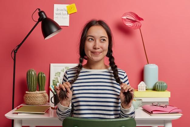 Nadenkend hipster meisje dingen over ideeën voor onderzoekswerk, zit in coworking space tegen desktop met notebooks, map en boeken eromheen