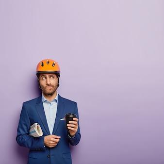 Nadenkend ingenieur drinkt afhaalkoffie, heeft pauze, draagt beschermende helm