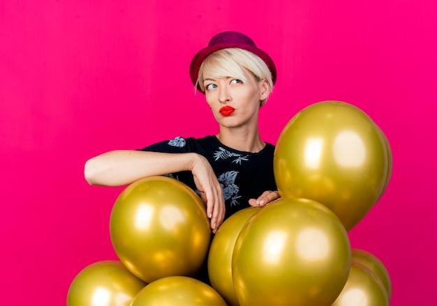 Nadenkend jong blond feestmeisje die feestmuts dragen die zich achter ballons bevinden die hen aanraken kijken kant geïsoleerd op karmozijnrode achtergrond