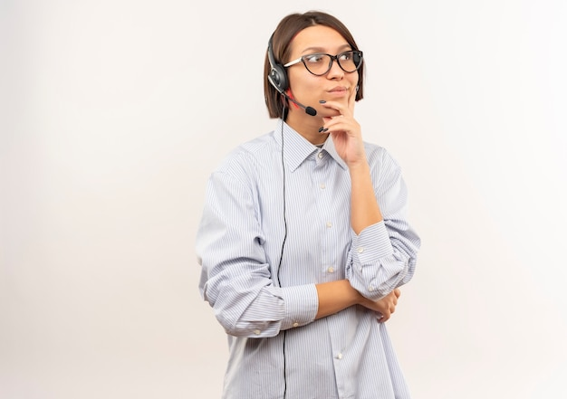 Nadenkend jong call centreermeisje die glazen en hoofdtelefoon dragen die kant bekijken die hand op kin zetten die op witte muur wordt geïsoleerd