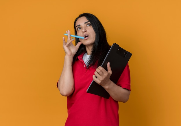 Nadenkend jong donkerbruin kaukasisch meisje dat rood overhemd draagt, zet pen op mond en houdt klembord dat op oranje muur wordt geïsoleerd
