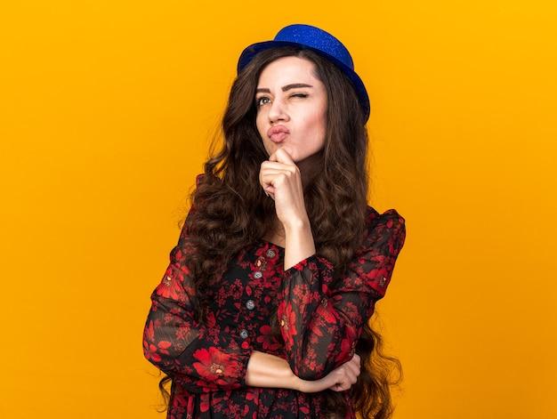 Nadenkend jong feestmeisje met feestmuts opkijkend hand op kin tuitende lippen met één oog gesloten geïsoleerd op oranje muur met kopieerruimte
