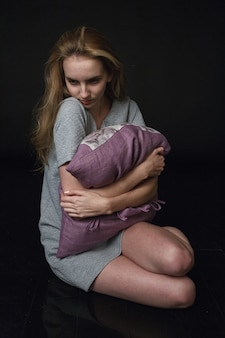 Nadenkend jong kaukasisch mager mooi meisje in grijze jurk zittend op de vloer, knuffelend paars kussen