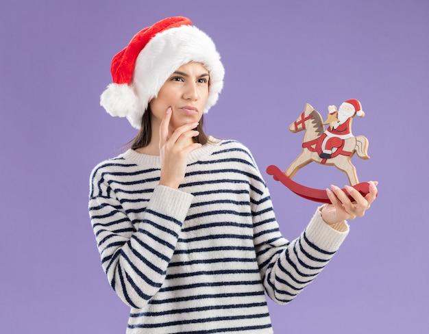 Nadenkend jong kaukasisch meisje met kerstmuts legt hand op kin en houdt santa op hobbelpaarddecoratie kant kijken