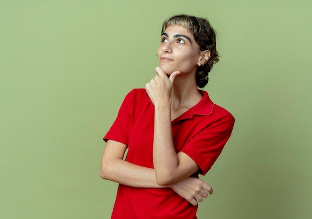 Nadenkend jong kaukasisch meisje met pixiekapsel die hand op kin zetten die omhoog geïsoleerd op olijfgroene achtergrond met exemplaarruimte kijken