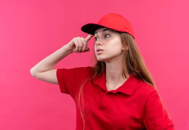 Nadenkend jong leveringsmeisje die in rood uniform vinger op hoofd zetten die linkerkant op geïsoleerde roze muur bekijken