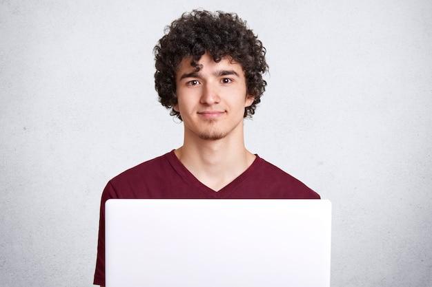 Nadenkend jong mannetje met krullend haar, kijkt rechtstreeks naar de camera, gebruikt moderne witte draagbare computer, gekleed casual kastanjebruin t-shirt, zit tegen witte betonnen muur met lege ruimte voor reclame.