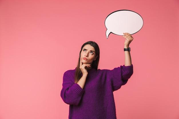 Nadenkend jong meisje dat sweater draagt die zich geïsoleerd over roze bevindt, die lege toespraakbel houdt