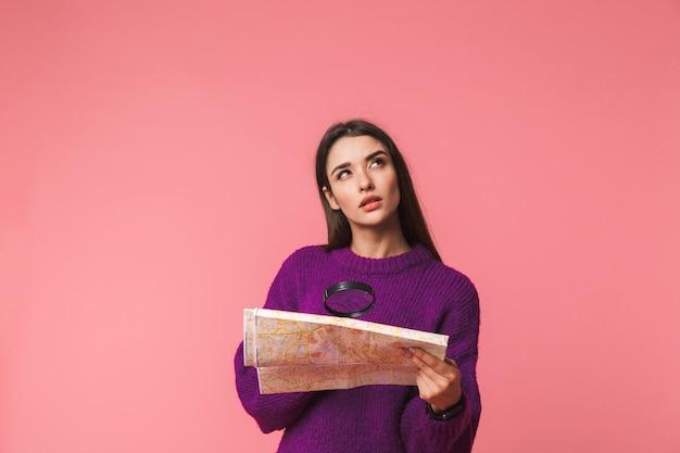 Nadenkend jong meisje dat trui draagt die zich geïsoleerd over roze bevindt, die door een vergrootglas naar een gidskaart kijkt
