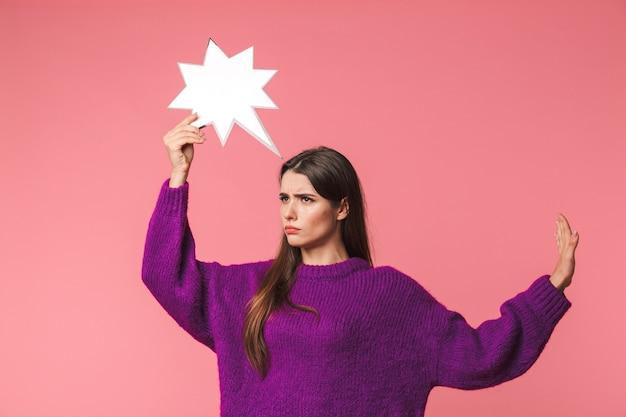 Nadenkend jong meisje dat trui draagt die zich geïsoleerd over roze bevindt, die lege toespraakbel, uitgestrekte hand houdt