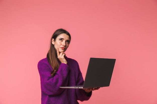 Nadenkend jong meisje dat trui draagt die zich geïsoleerd over roze bevindt, laptop computer houdt