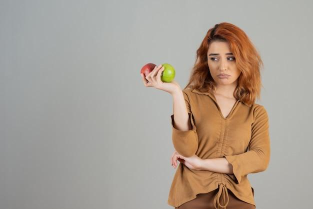 Nadenkend jong meisje op zoek naar verse appels in haar handen op grijs.