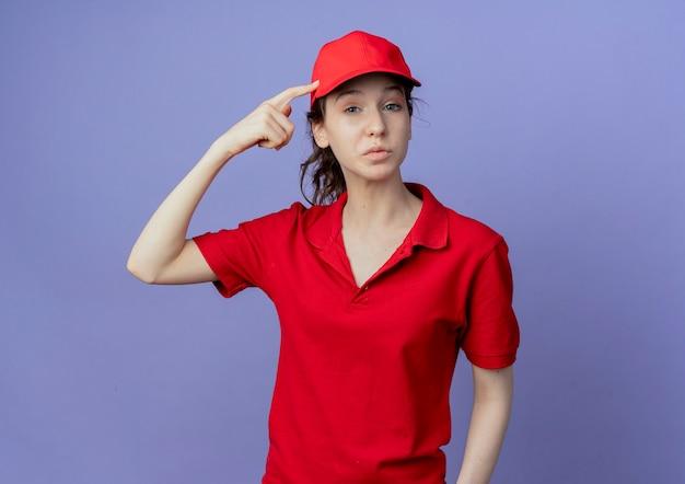 Nadenkend jong mooi leveringsmeisje die rood uniform en glb dragen die vinger op hoofd zetten dat op purpere achtergrond wordt geïsoleerd