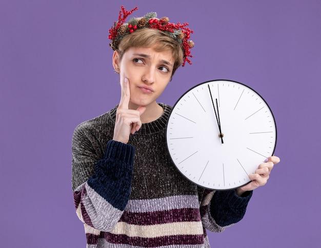 Nadenkend jong mooi meisje die de holdingsklok van de kerstmis hoofdkroon dragen die hand op kin houden die kant bekijken die op purpere achtergrond wordt geïsoleerd