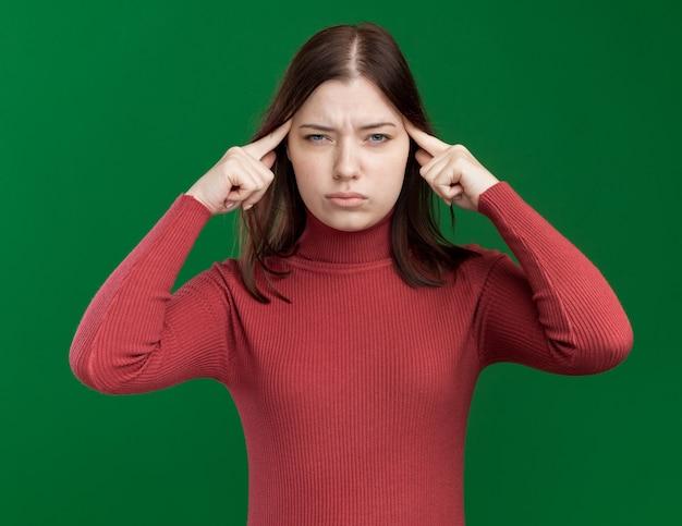 Nadenkend jong mooi meisje doet denk gebaar geïsoleerd op groene muur