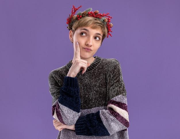 Nadenkend jong mooi meisje met een kersthoofdkrans die het gezicht aanraakt en naar de kant kijkt die op een paarse muur met kopieerruimte is geïsoleerd