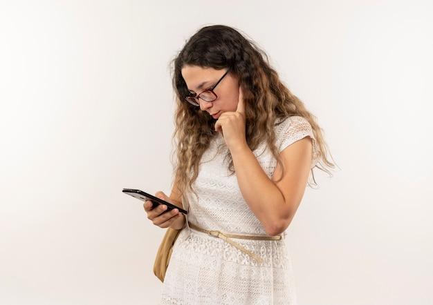 Nadenkend jong mooi schoolmeisje die glazen en rugtas dragen die haar telefoon met hand op kin zetten die op witte muur wordt geïsoleerd