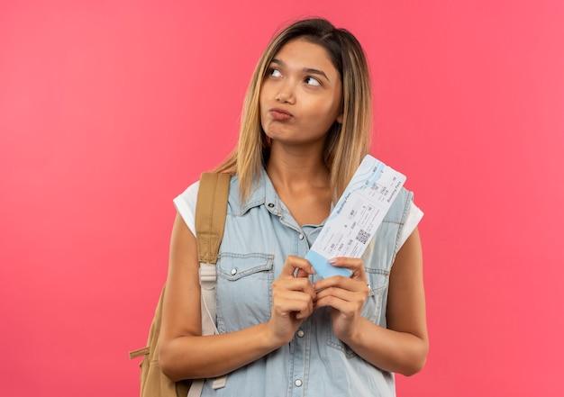 Nadenkend jong mooi studentenmeisje die het vliegtuigticket van de achterzak dragen die kant bekijken die op roze muur wordt geïsoleerd