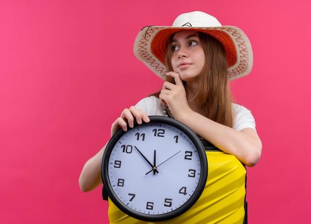Nadenkend jong reizigersmeisje die hoed dragen die klok houden en arm op koffer en vinger op kin zetten die naar linkerkant op geïsoleerde roze muur met exemplaarruimte kijken
