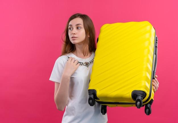 Nadenkend jong reizigersmeisje die koffer houden en hand op borst zetten die naar linkerkant op geïsoleerde roze muur met exemplaarruimte kijken