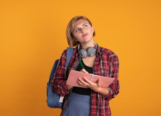 Nadenkend jong slavisch studentenmeisje met hoofdtelefoon die rugzak draagt houdt notitieboekje en pen omhoog kijkend