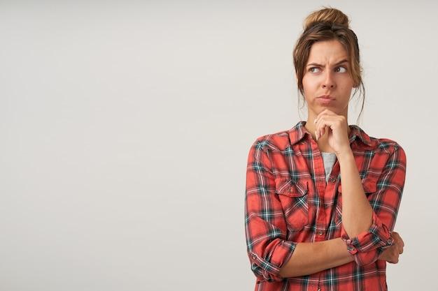 Nadenkend jonge aantrekkelijke bruinharige dame met natuurlijke make-up leunend met haar kin op opgeheven hand terwijl ze somber opzij kijkt, geïsoleerd op witte achtergrond