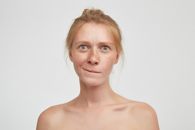 Nadenkend jonge aantrekkelijke roodharige vrouw met broodje kapsel bijten onderlip en verward kijken naar camera, poseren op witte achtergrond met blote schouders