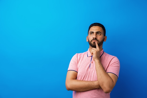 Nadenkend jonge arabische man denken en kijken tegen blauwe achtergrond