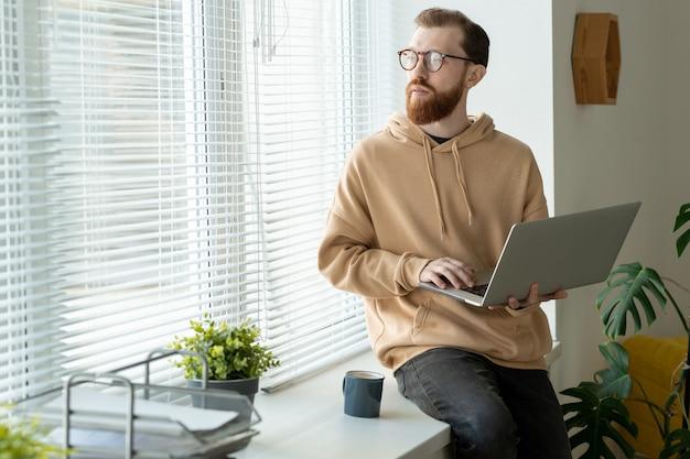 Nadenkend jonge bebaarde man in hoodie zittend op de vensterbank en laptop vast te houden terwijl hij aan design denkt