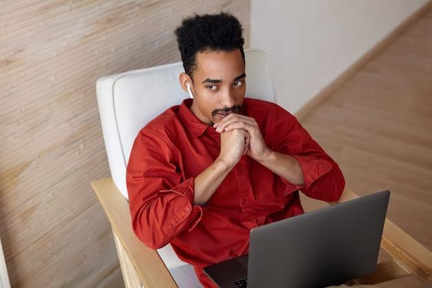 Nadenkend jonge bruinogige kortharige, bebaarde man met donkere huid, zijn kin op gevouwen handen leunend en bedachtzaam uit het raam kijken tijdens een videogesprek
