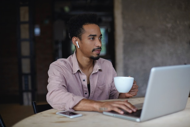 Nadenkend jonge donkere bebaarde man met een draadloze koptelefoon in zijn oren bedachtzaam opzij kijken terwijl het drinken van een kopje koffie, zittend over stadscafé met moderne laptop