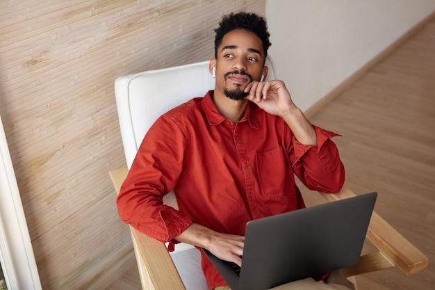 Nadenkend jonge kortharige brunette man met donkere huid met opgeheven hand op zijn gezicht en luisteren naar muziek in zijn koptelefoon terwijl hij pauze maakt met werk
