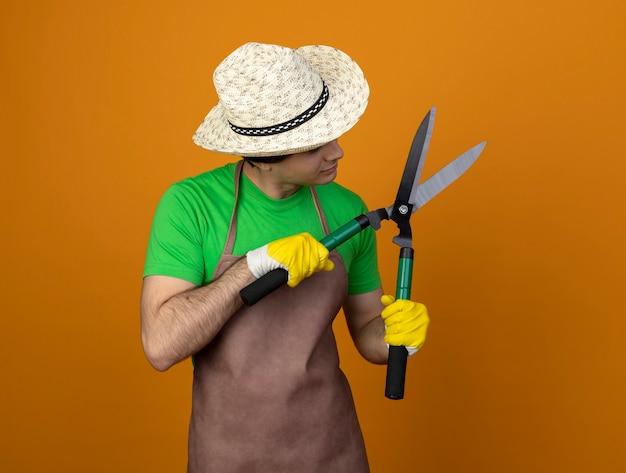 Nadenkend jonge mannelijke tuinman in uniform dragen tuinieren hoed met handschoenen houden en kijken naar tondeuse geïsoleerd op oranje