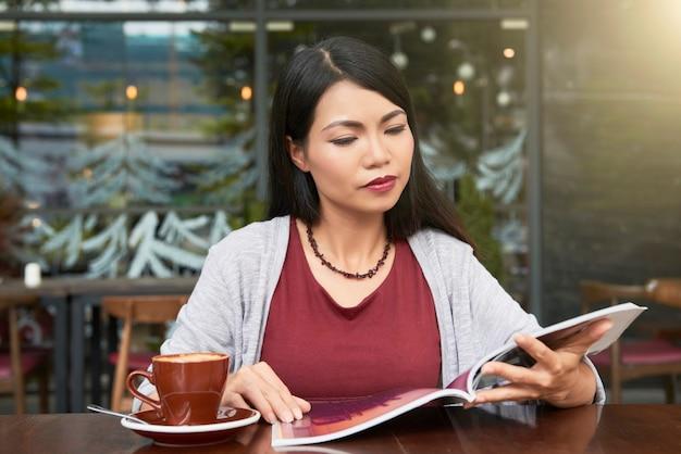Nadenkend jonge mooie aziatische vrouw kopje koffie drinken en tijdschrift lezen in coffeeshop