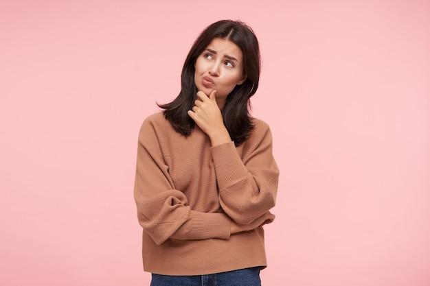 Nadenkend jonge mooie bruinharige vrouw met losse haren die haar kin vasthoudt met opgeheven hand en bedachtzaam naar boven kijkt, staande over roze muur