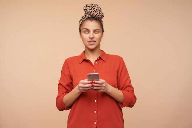 Nadenkend jonge mooie brunette vrouw met hoofdband smartphone in opgeheven handen houden en bedachtzaam opzij kijken, geïsoleerd over beige muur