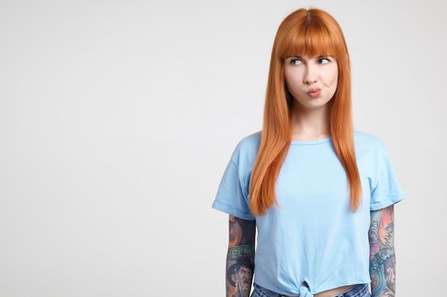 Nadenkend jonge mooie roodharige getatoeëerde vrouw kijkt ernstig opzij en draait haar mond terwijl ze tegen een witte achtergrond in een blauw t-shirt staat