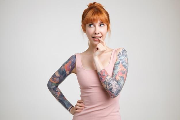 Nadenkend jonge mooie roodharige vrouw met tatoeages die wijsvinger op haar onderlip houden terwijl ze verwonderd opzij kijkt, staande op een witte achtergrond