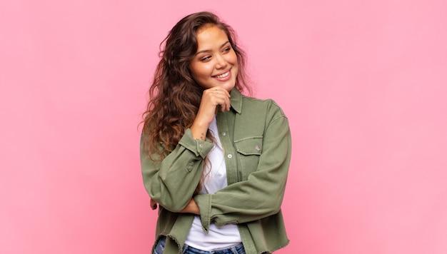 Nadenkend jonge mooie vrouw op roze achtergrond