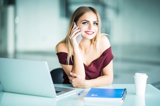 Nadenkend jonge vrouw bellen naar exploitant van software voor het bijwerken van klantenondersteuning op laptopcomputer in kantoor. ernstige vrouwelijke freelancer concentreerde zich op telefoongesprekken over online zaken