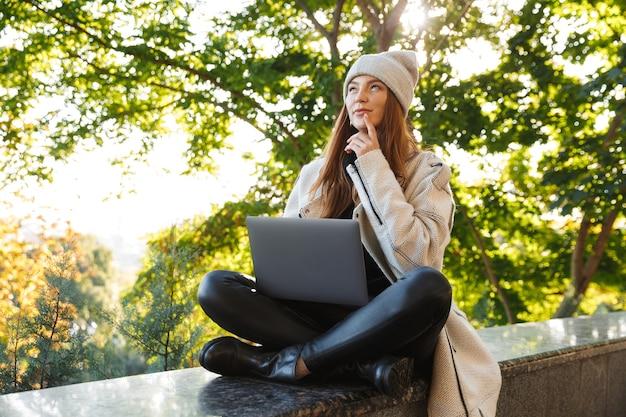 Nadenkend jonge vrouw gekleed in herfst jas en hoed buiten zitten met lap top computer