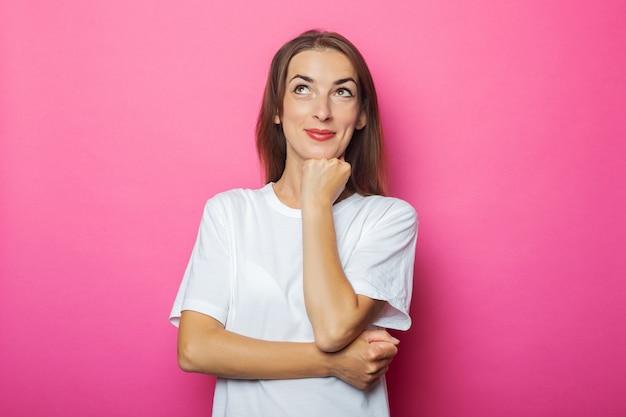 Nadenkend jonge vrouw in wit t-shirt houdt hand onder de kin